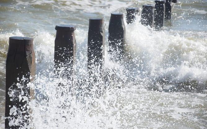 Ocean waves crash and spray against wavebreakers.