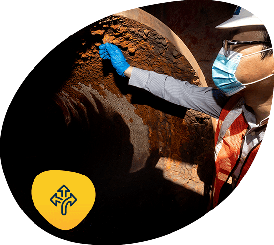 Person examines rusted interior of a water pipe with icon for adaptation strategic direction